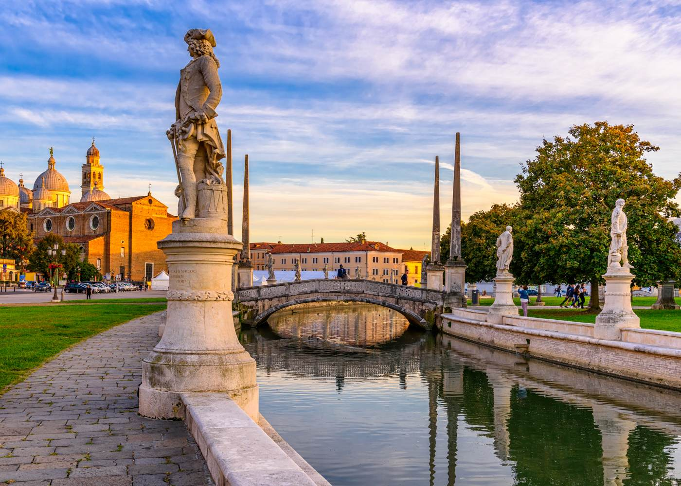 Canal with statues on square Prato della Valle and Basilica Santa Giustina
